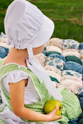 amish child sitting on Amish quilt